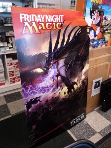 A cardboard standee advertising the Dragons of Tarkir expansion and Friday Night Magic events at hobby shops.
