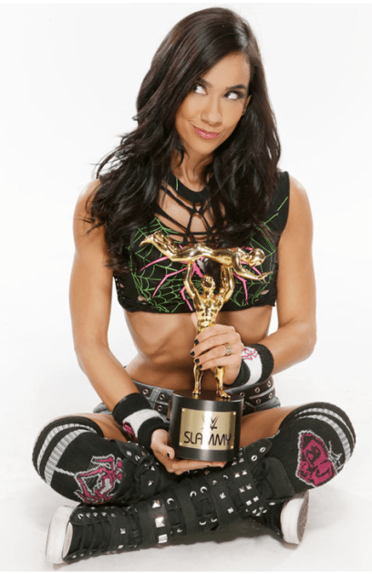 AJ Brooks, a tanned dark-haired woman, sitting with a trophy.
