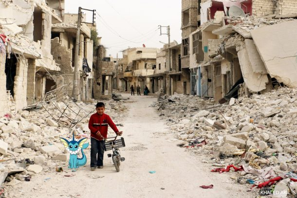 A Syrian boy walks with his bicycle in the devastated Sukari district in the northern city of Aleppo. Credits: Khaled Akil