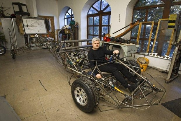 Stefan Klein poses in the skeletal frame of the flying car. You can see the driveshafts fr...