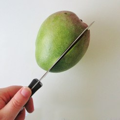 "Cheek 1: Mangos have two wide sides (cheeks) and new narrow sides (fingers), with an oblong pit in the the middle that runs the length of the whole fruit. To cut your first cheek, line up your knife 1/2"" to 1"" from the center and make a lengthwise cut straight through."