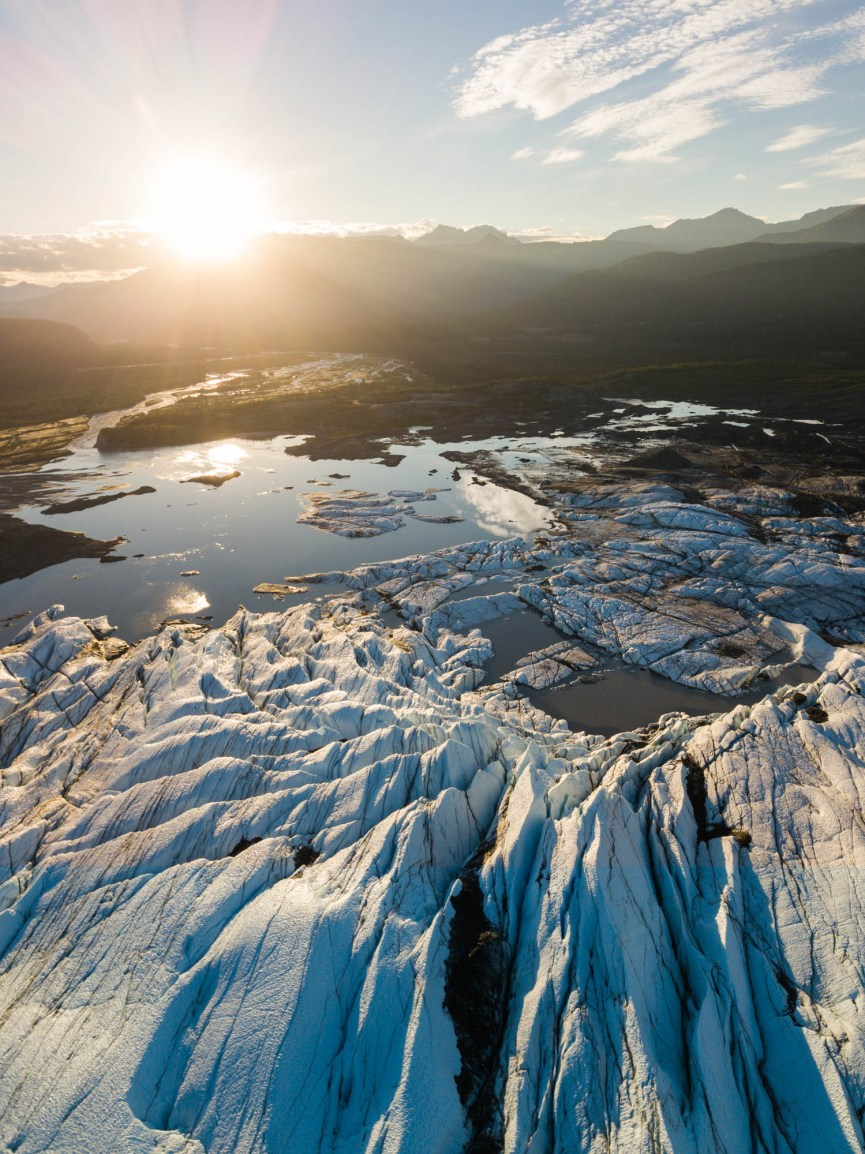 An aerial view of Matanuska glacier and its jagged crevasses as a bright sun begins to set on the horizon. The melting glacier forms a small lake at its end.