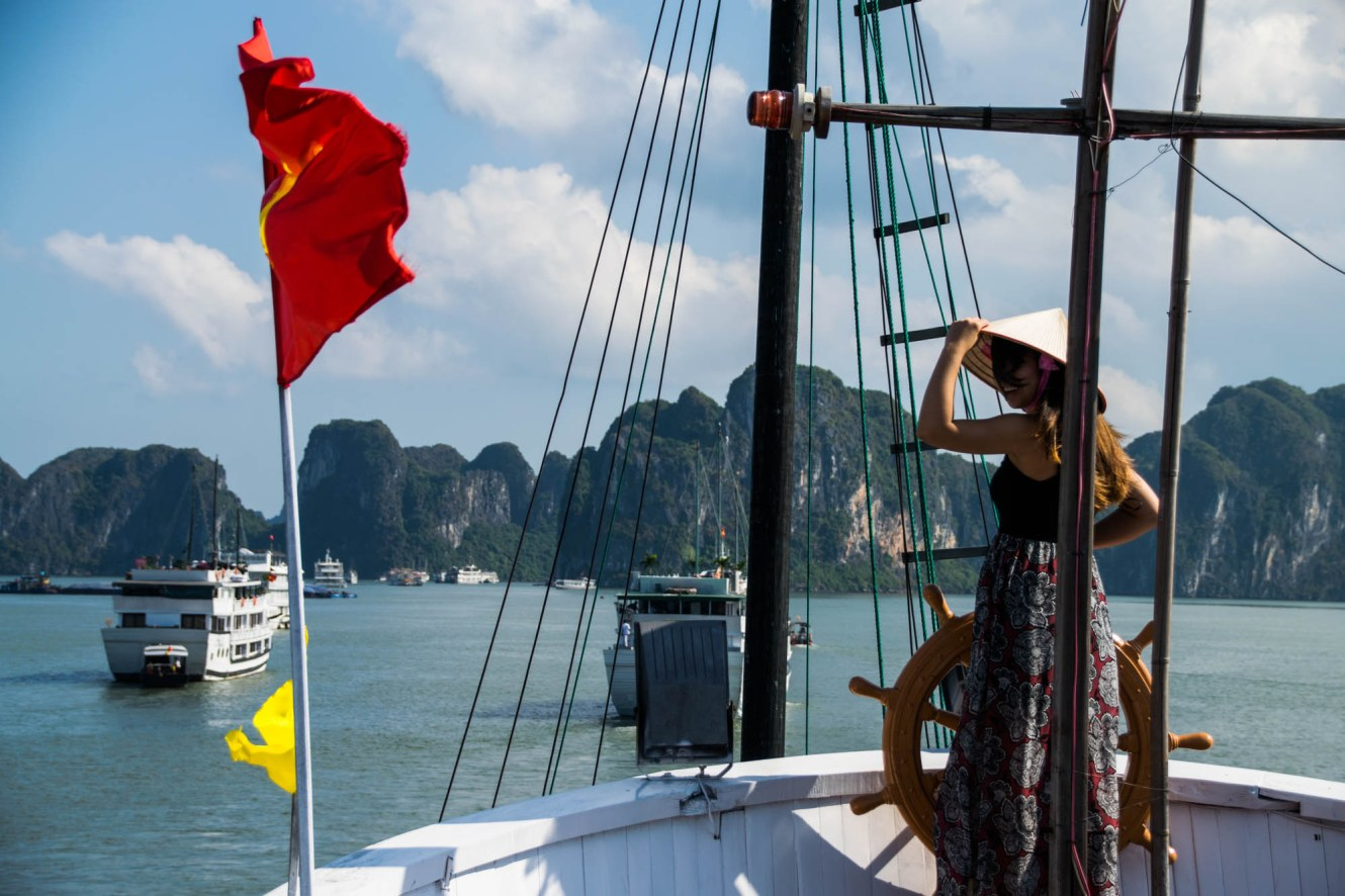 A young asian woman wearing a pointy conical straw hat steers the ship's wheel and smiles as the wind blows her hair into her face. The vietnamese flag is blowing in the wind and there are mountains in the background. There is a strong sense of travel adventure.