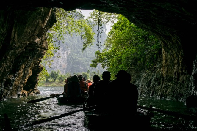 A group of small boats row are sillohuetted as the row out of a dark river cave toward large mountain jungle cliffs in Tam Coc, Vietnam