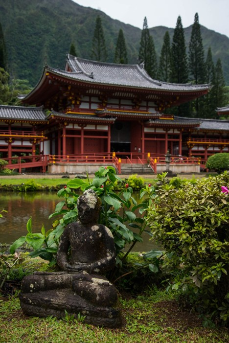 A small stone statue of a person in full lotus meditating position is placed in a garden. A red chinese buddhist temple is seen in the background among tall trees and towering mountains. Seen in Hawaii.