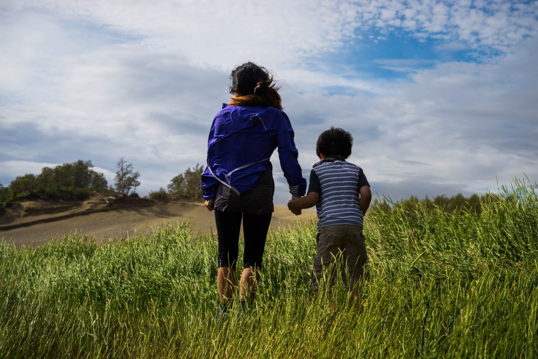 A young boy tightly holds his mother's hand as stong wind gusts and they navigate through tall grass.