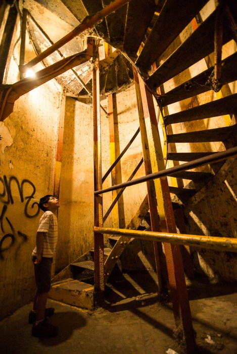 A young boy is inspecting an old metal spiral staircase laced with spider webs. He seems curious yet cautious.