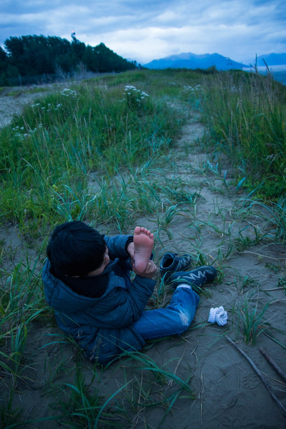 A young boy sits down on the middle of an alaskan trail as he removes his shoe and sock to inspect his foot for rocks and sand. Its midnight in alaska but the sun is still out and it appears to be twilight. Near Jodhpur sand dunes.