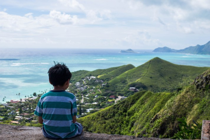 A young boy sits on an old bunker along the Pillbox hike near Lanakai Hawai and overlooks a beautiful scene of green mountains and turquoise ocean