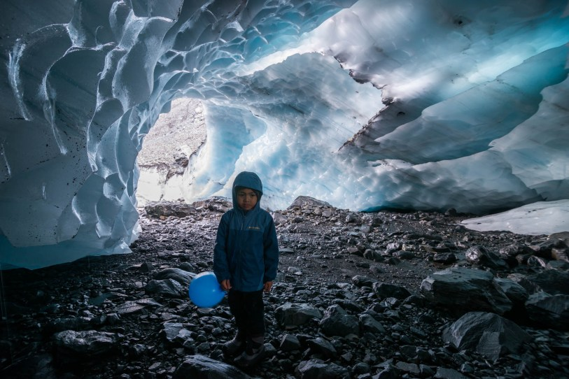 A 5 year old boy explores a glacier cave with blue ice. He is holding a balloon and looks slightly sad, tired and cold.