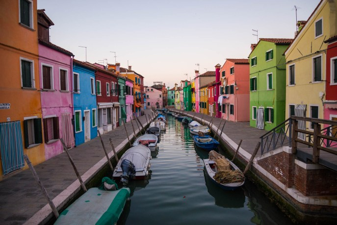 Colorful houses are seen at twilight divided by a waterway canal in the small town of Burano in italy near venice. Boats line the canal and the streets are empty as everyone is in for dinner.