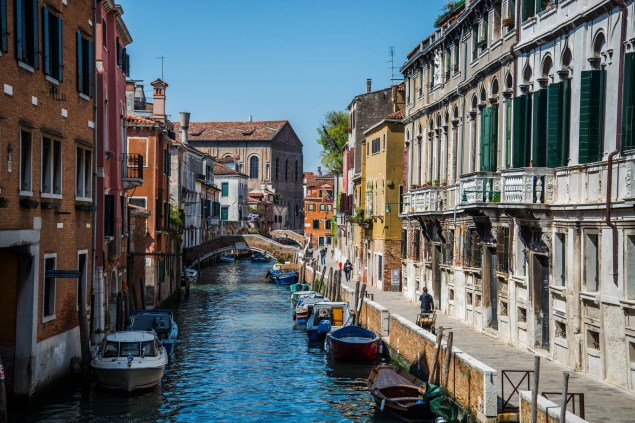 A colorful scene of a venice canal and ally way. Boats are parked on the edges of the canal and people walk the ally way.