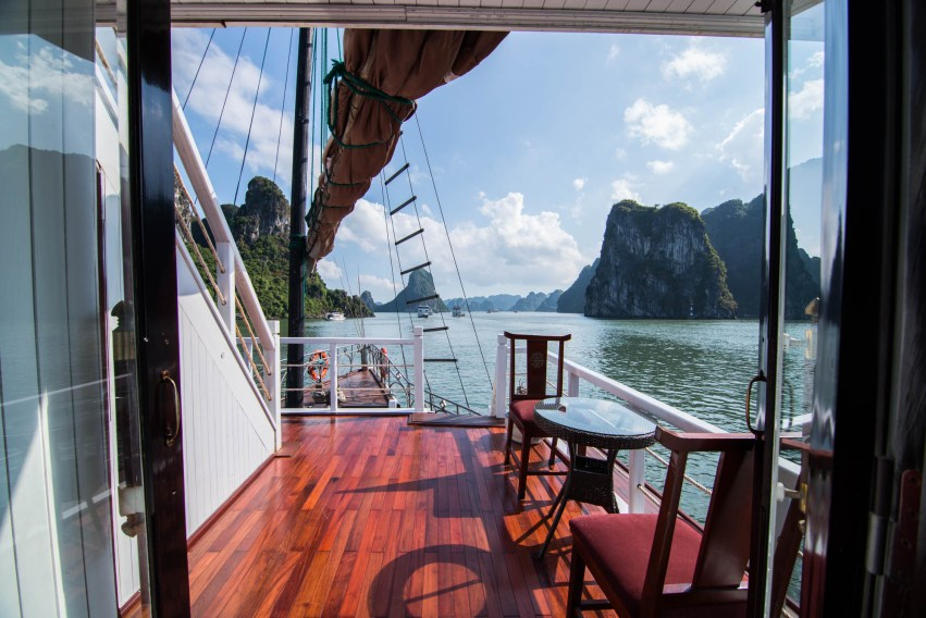 A cruise boats doors open to hardwood floors, a sailing boast mast, a coffee table to relax and Vietnam's sunny Halong Bay. There is a strong sense of travel adventure.