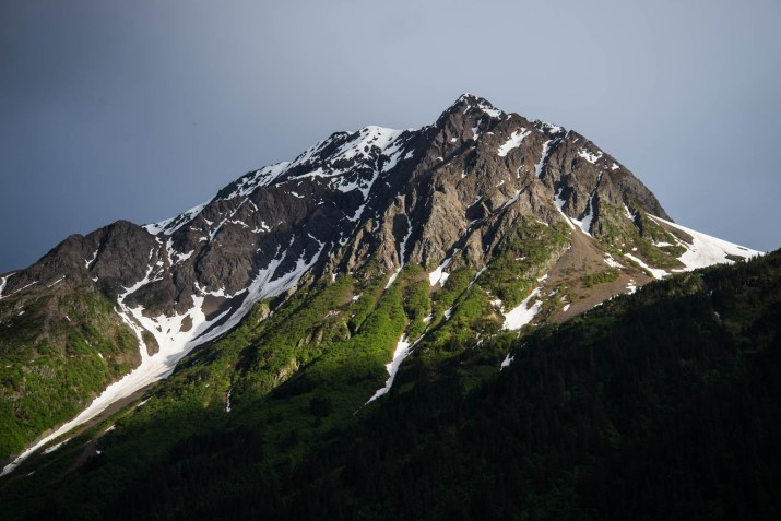 A mountain peak rises above the shadows and into the sunlight against a gray sky . The green forest climbs up most the mountain then stops below the bare rock of the mountain peak. Snow remains in somw of the mountain's crevases.