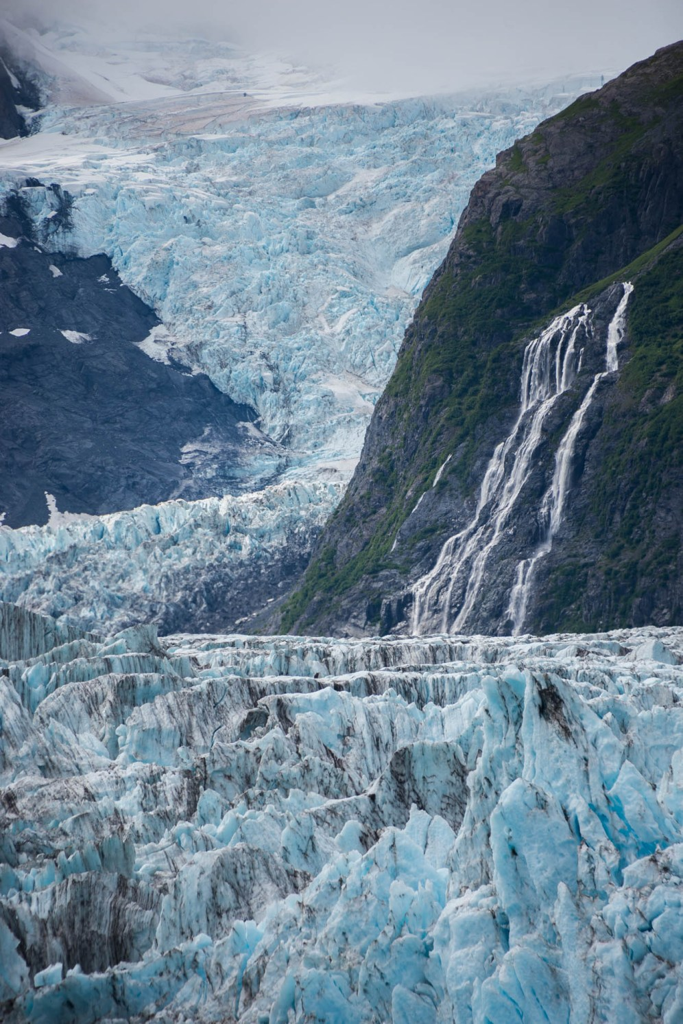 A large and long mass of ice known as surprise glacier decends from cloud cover and down a mountain. Along the way it meets with a cascading waterfall. Orientation is vertical