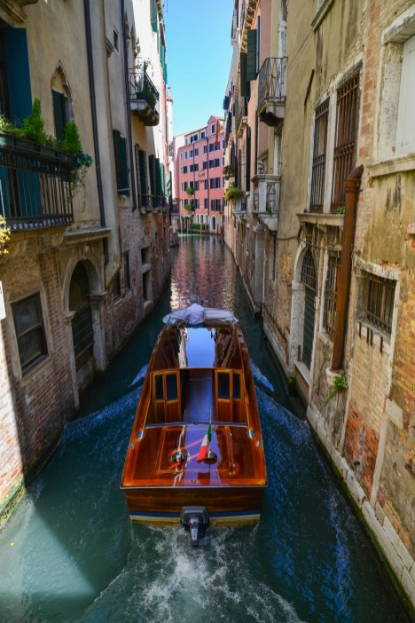 A fine highly polished wooden boat with an italian flag powers through the narrow canals of venice.