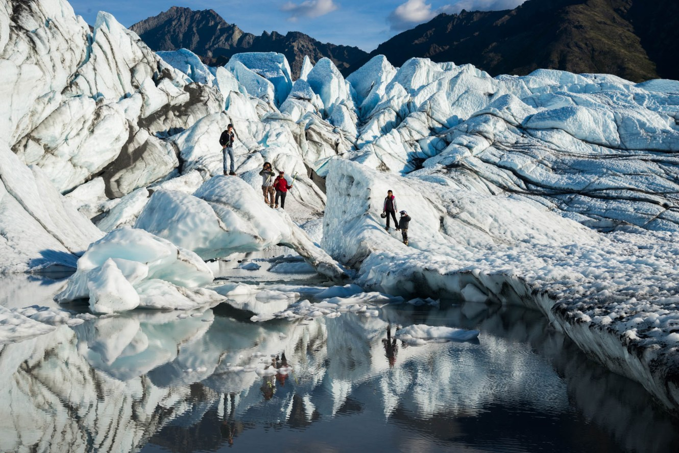 A group of friends climb on a natural ice bridge over a reflecting lake on Alaska's Matanuska glacier.