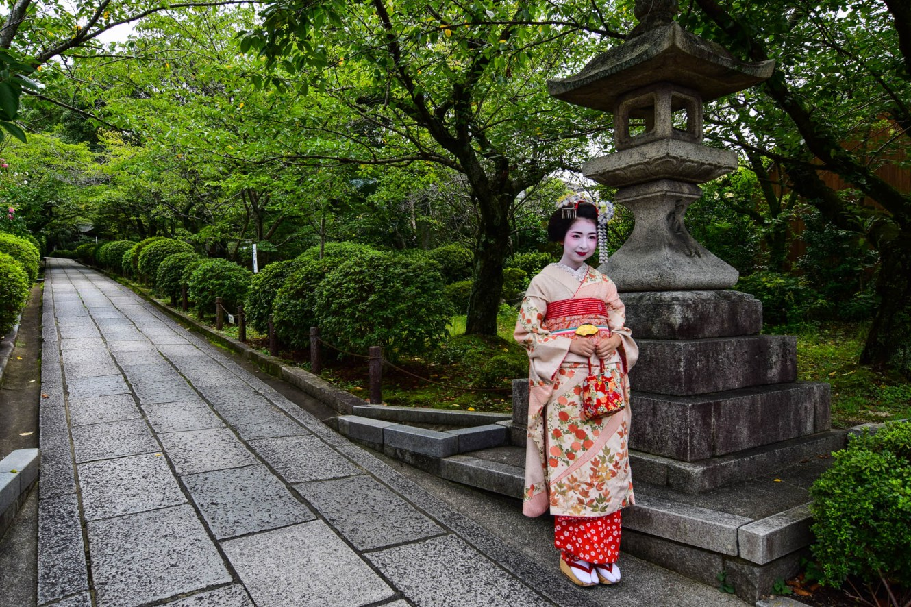 An apprentice Geisha poses along the entrance to a stone path that leads to a garden. She wears a traditional pink floral kimono, okobo footwear and a white face.