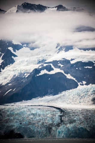A large glacier decends down a mountain through clouds and into the ocean. The scene is dark with with shades of blue and grey.