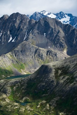 A glacial lake in a hanging valley is shown from the vantage point of Harp mountain in the Chugach mountains behind Eagle River, Alaska. The scene is pure alpine wilderness.