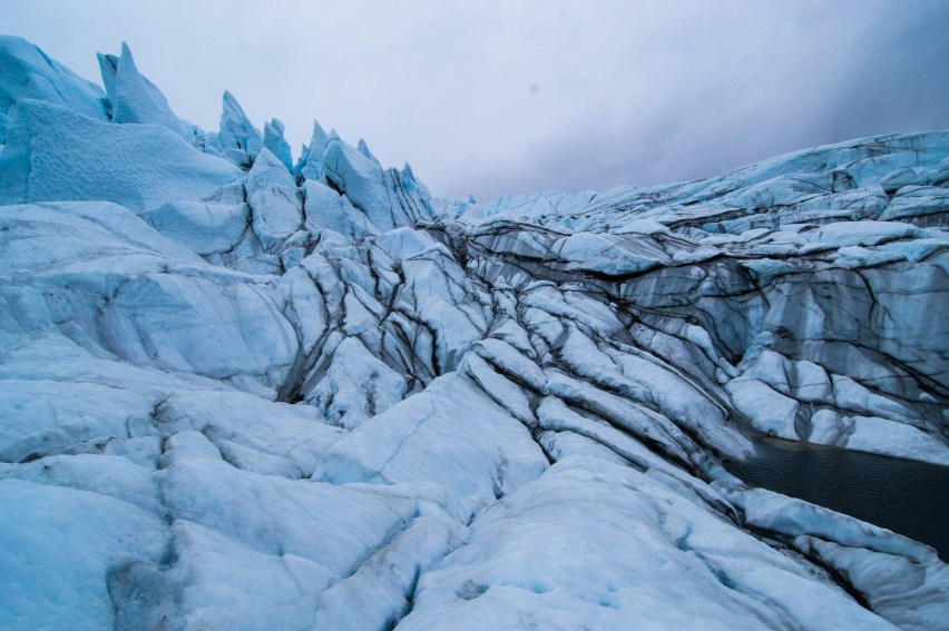 The jagged and dramatic Matanuska glacier is shown with viens of dark crush sediment in between blue slabs of ice under a grey sky.