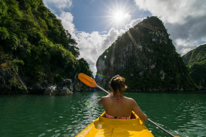 A young woman is seen from behind as she paddles her kayak in Vietnam's Ha Long bay. The sun is seen bursting from the clouds radiating rays of light in all directions.