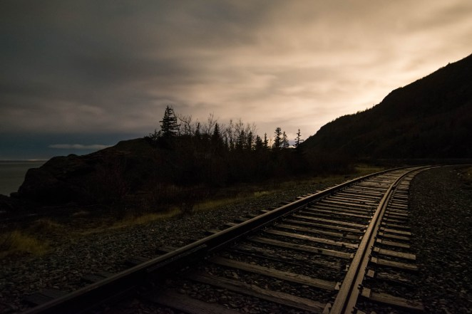 The alaska railroad is seen at night near Beluga point. The clouds refelct the moonlight onto the train tracks.