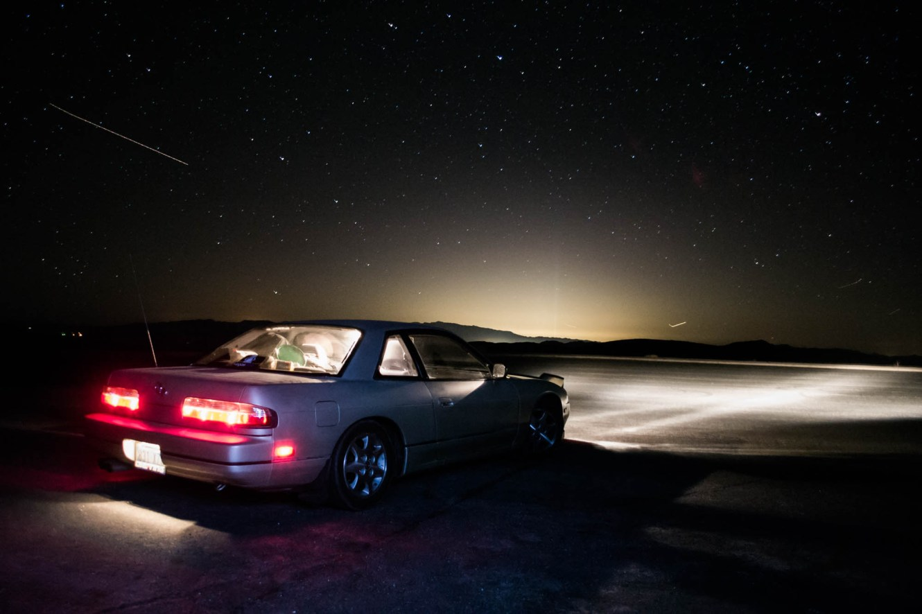 A nissan 240sx pauses in Death valley under a shooting star and looks back at the light pollution from Las Vegas