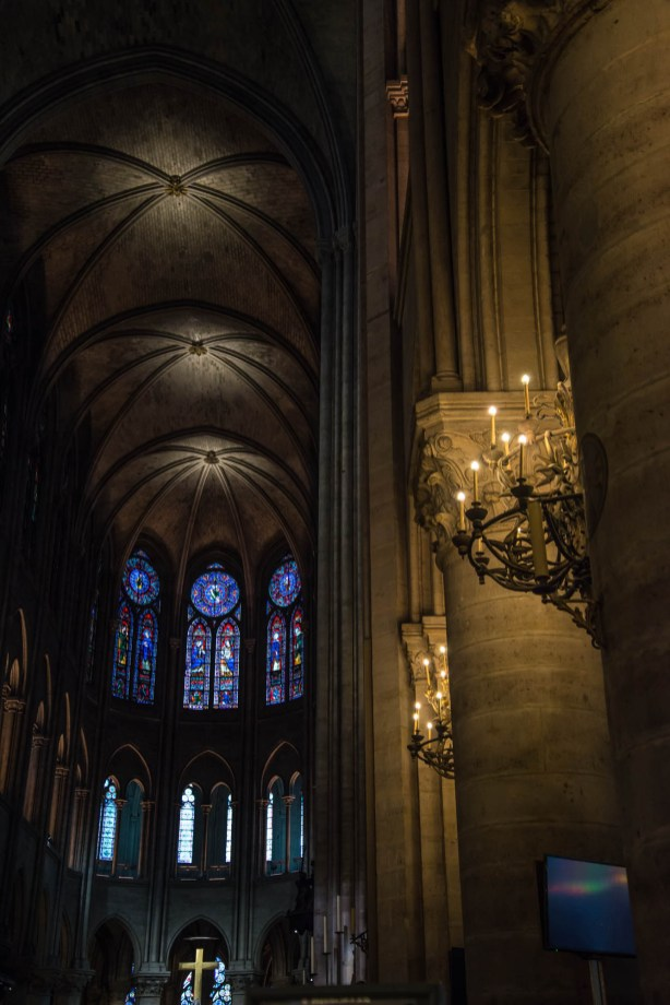 The interior of the Notre Dame cathedral is seen. Candles light up the stone pillars and the main crucifix is seen illuminated by stained glass.