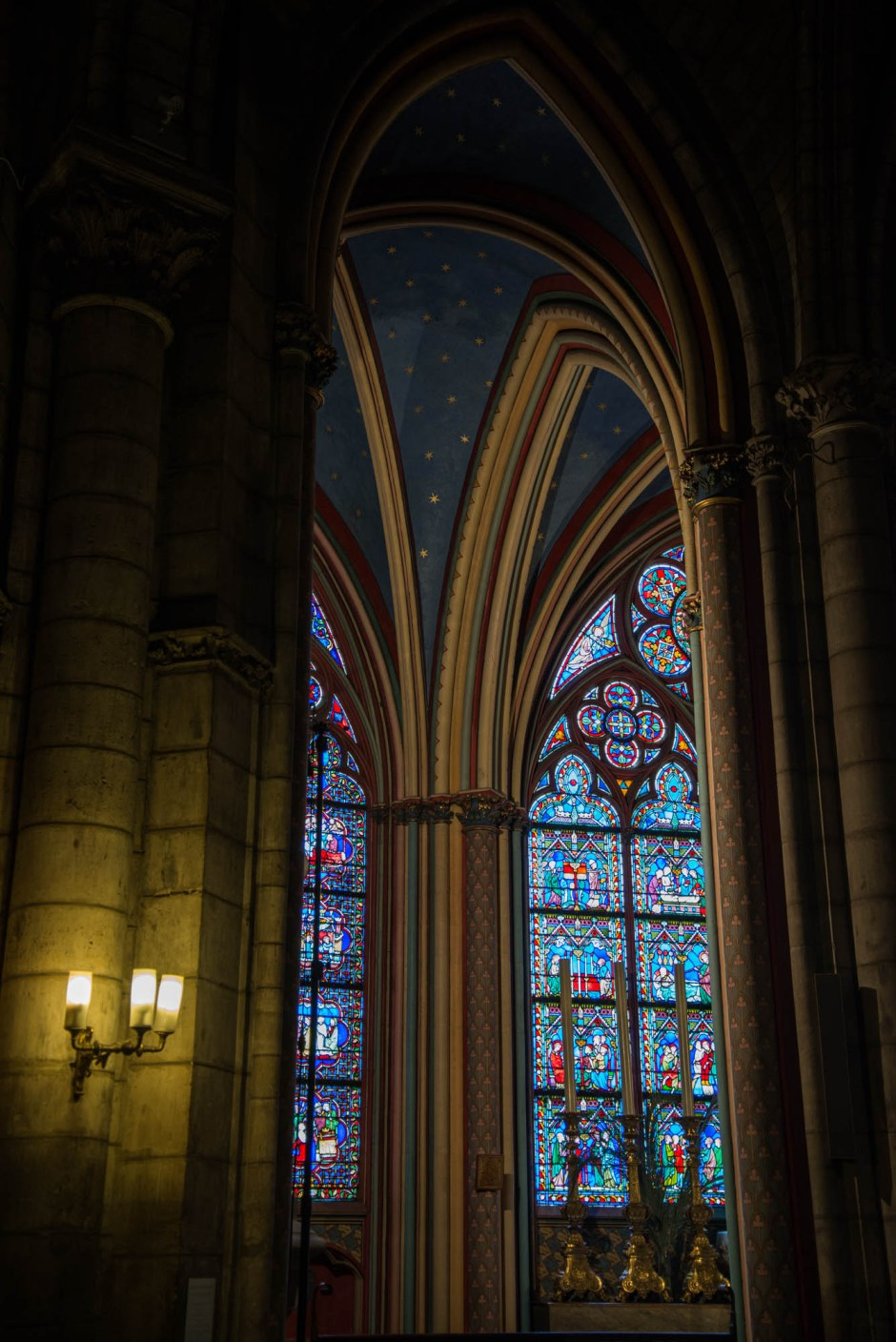 The colorfull arches and roof of the Notre Dame catherdral are seen illuminated by intricate stained glass windows and candlelight