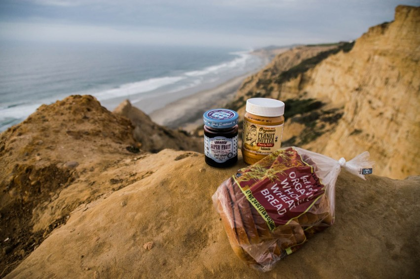 Organic bread, peanut butter and jelly are perched over San Diego's Ocean cliffs in preparation for and extreme picnic.