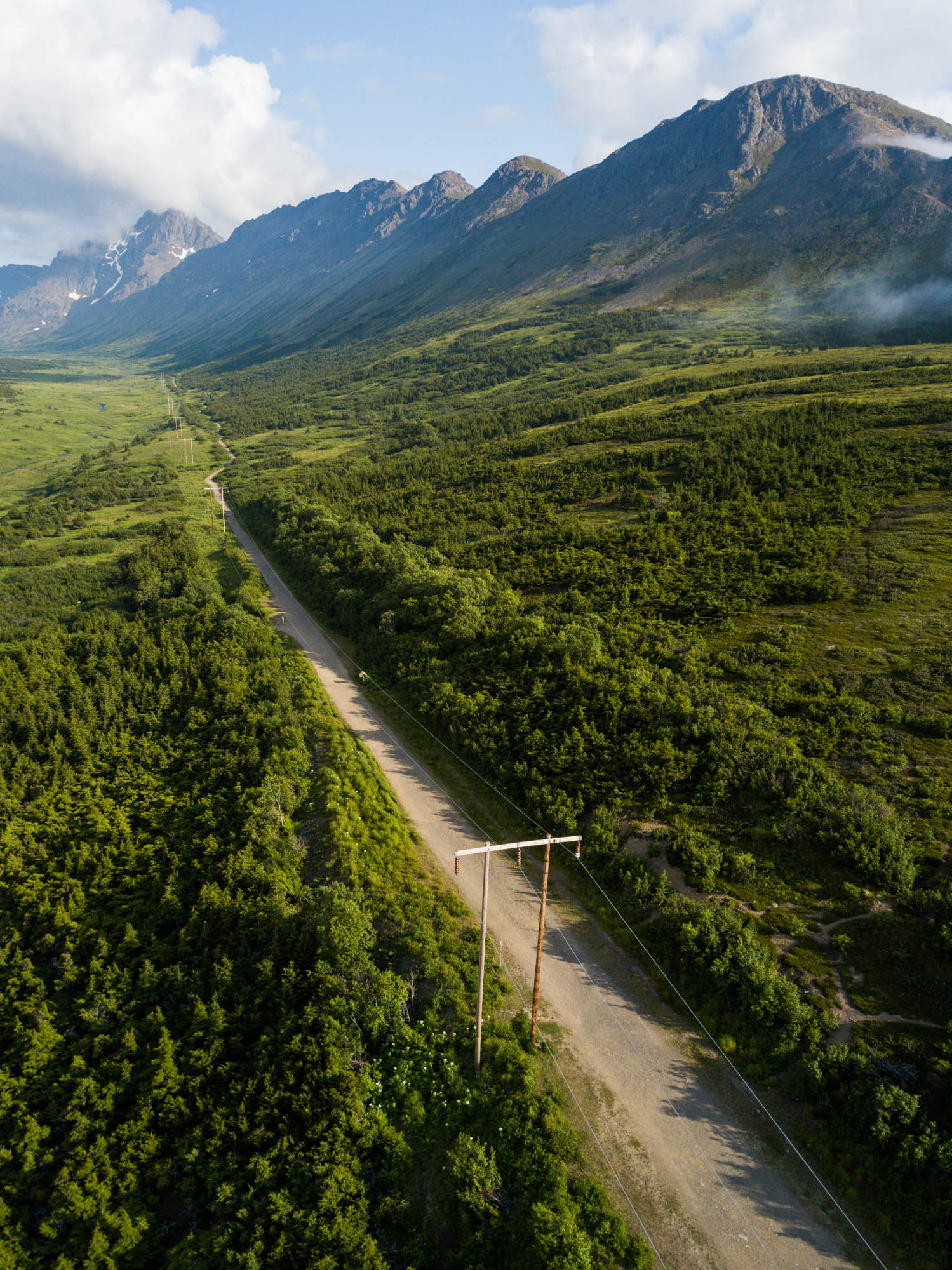 The powerline pass trail is seen from above as it cuts through a forested mountain valley near Anchorage, Alaska. It is a bright partly cloudy summer day. Orientation is vertical.