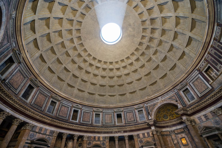 The ancient Pantheon's concrete dome ceiling is seen from inside as a large ray of light shines through the center.