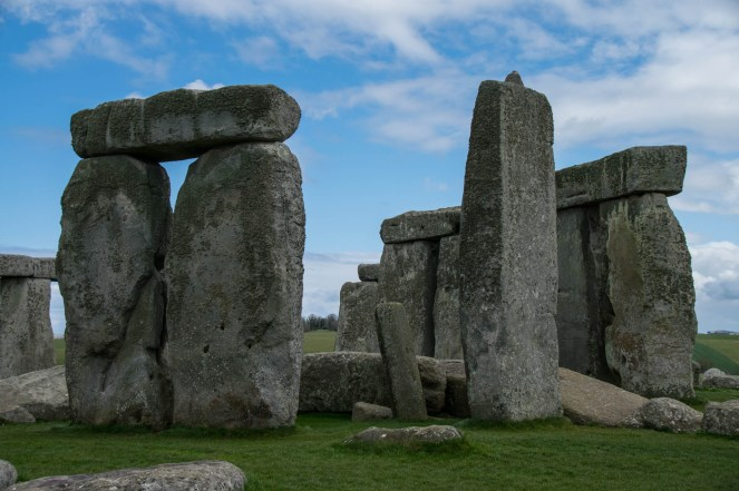 A close view of Stonehenge is seen with a partly cloudy and blue sky