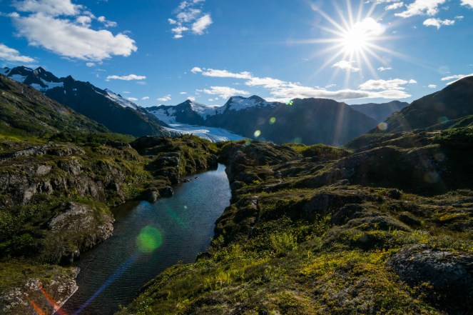 A small alpine pond, surrounded by bright green plants, sits on top of Portage Pass in Alaska. Rays of sunlight radiate in all directions and cause a sun flare effect. Portage glacier is seen in the background among mountains.