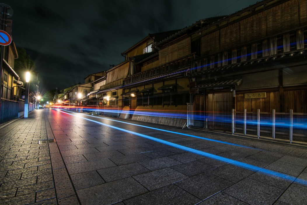 Traditional wooden Japanese buildings line a brick road in one of Tokyo's Geisha district at night. A long exposure of a passing car leaves headlight and taillight streaks