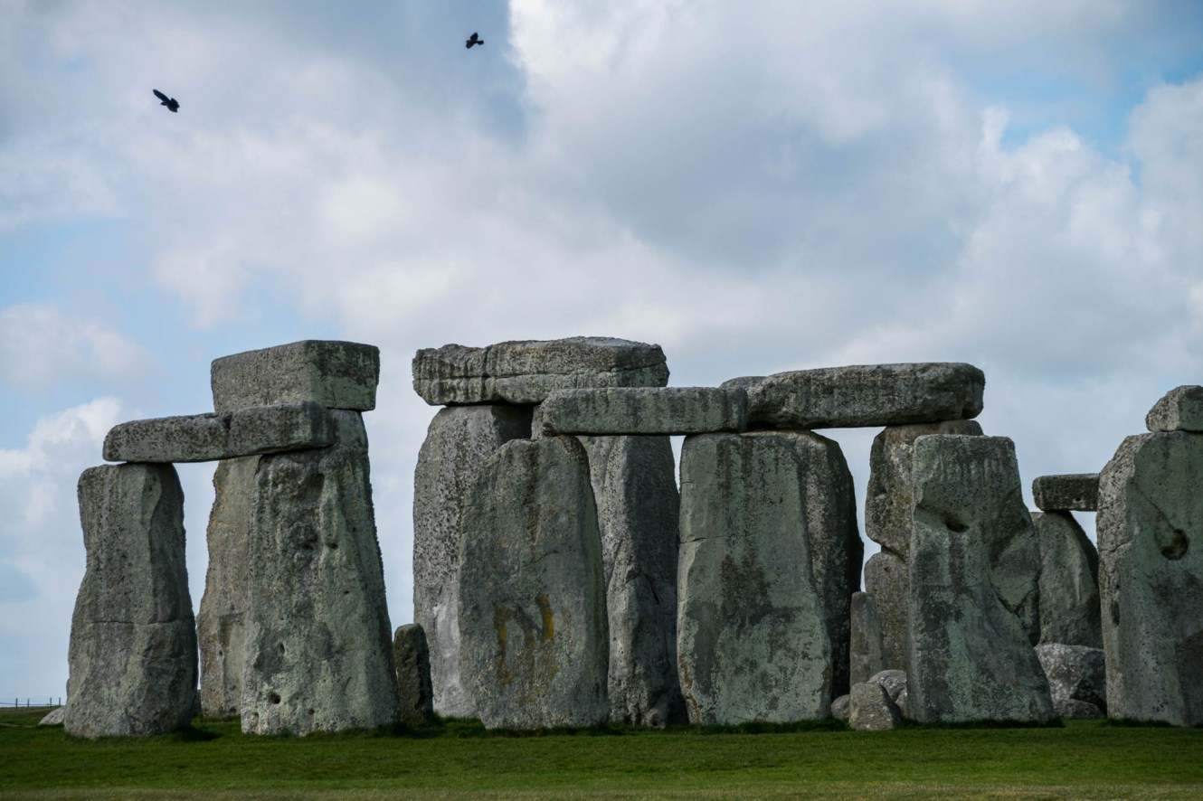 Two black crows fly over ancient empty Stonehenge on a partly cloudy day