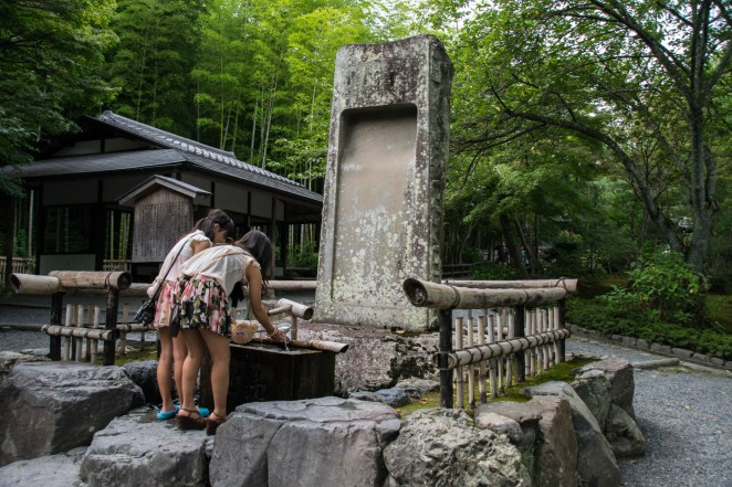 Two young japanese girls perform the cleasing ceremony at a shrine in one of Japan's gardens.