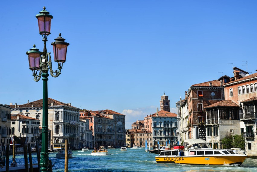 A sunny day scene is seen in one of venice's main water ways. Water taxis are seen in the background and a decorative street lamp in the foreground.