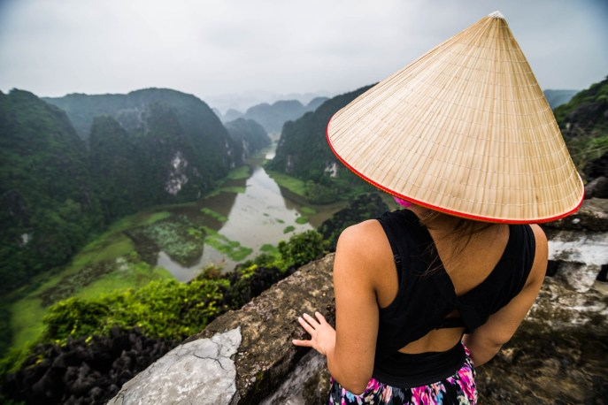A young asian woman wearing a pointy conical straw hat overlooks foggy mountains from a vantage point near Tam Coc in Vietnam.