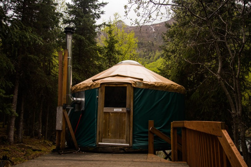 A cozy green and bown Yurt is seen perched on a deck deep in the forest near Eagle River Alaska
