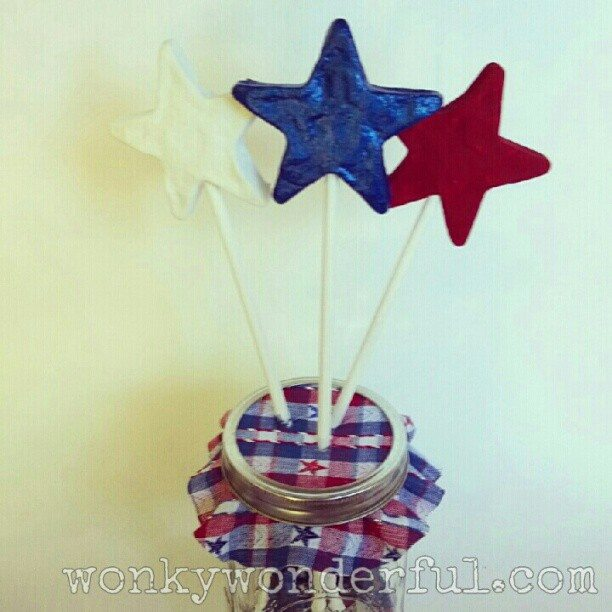 red, white and blue stars on sticks in glass jar with patriotic fabric on top