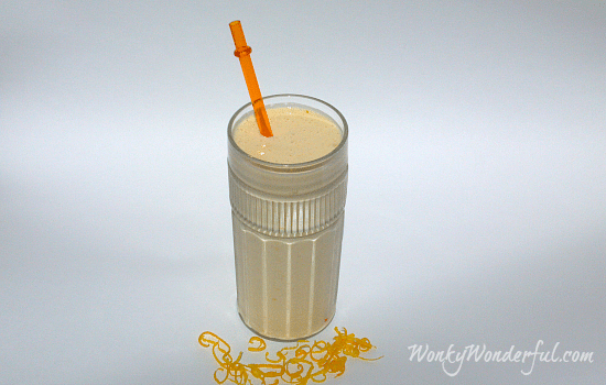 orange smoothie in clear glass with orange plastic straw