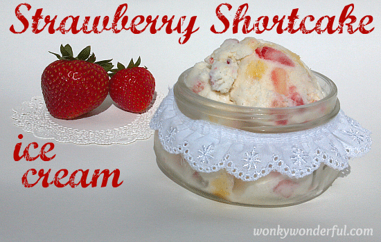 white ice cream with chunks of strawberries and cake in glass jar with two strawberries on the side