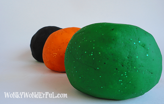 green, orange and black play dough balls in a row