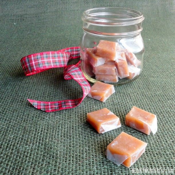 clear glass jar filled with caramels, wrapped caramels and ribbon on the side