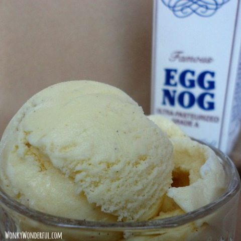 scoop of ice cream in clear glass bowl with eggnog carton in the background
