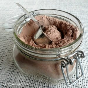 powdered cocoa mix in glass jar with metal scoop