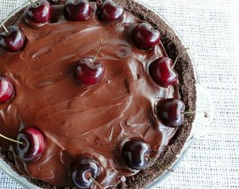 chocolate covered pie with fresh cherries arranged on top