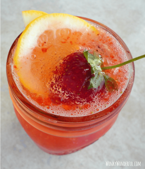 bubbly drink with lemon and strawberry on top in clear glass mason jar